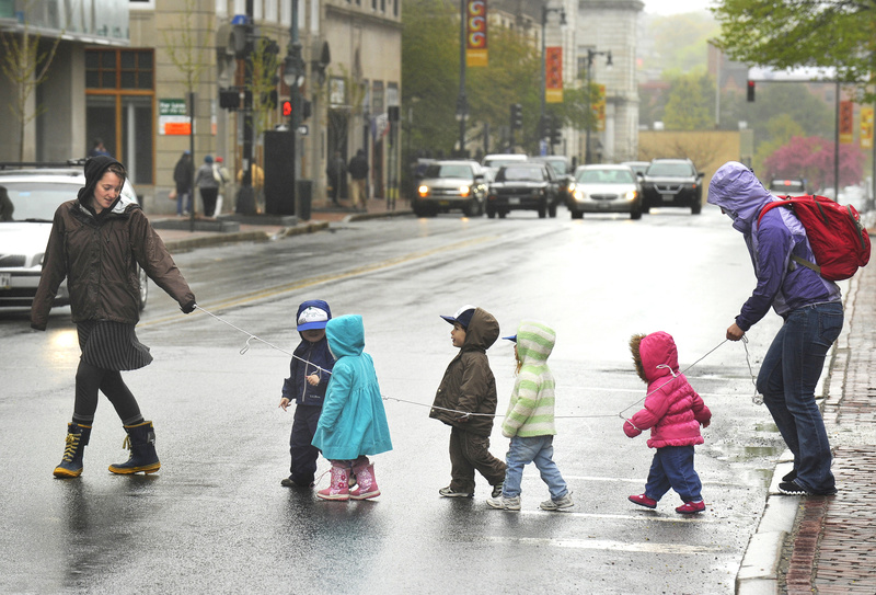 Teachers at the Youth and Family Outreach day care center lead some of their preschoolers across Congress Street on a dark and drizzly Monday morning after a walk around downtown Portland.