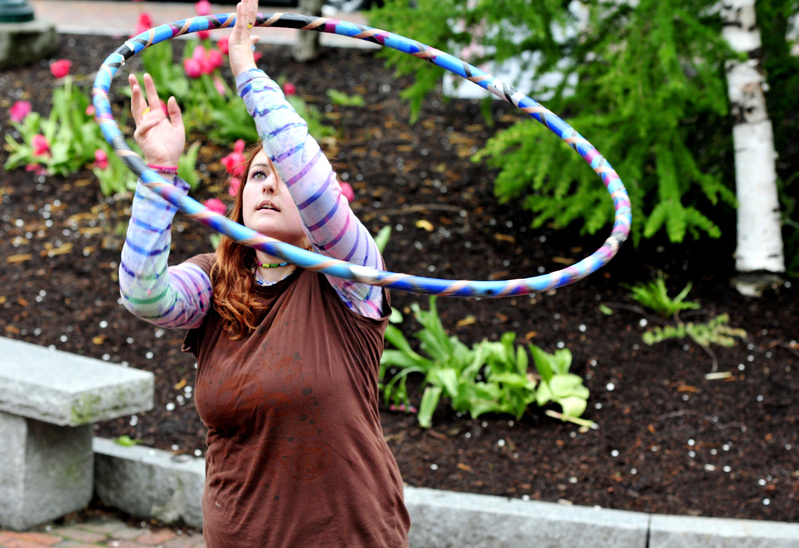 "Kerri Consiglio of Windham twirls an ""exercise hoop"" made with irrigation tubing and filled with water while hanging out Monday at Post Office Park in Portland."