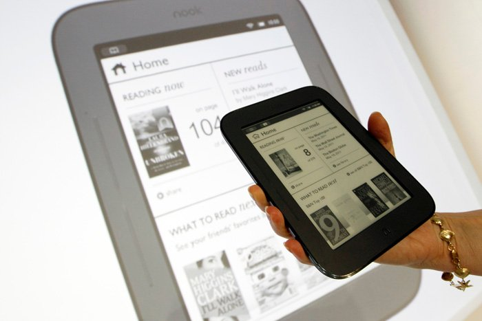 A product specialist holds up a new Nook during a news conference today in New York. The new Nook features a black-and-white touch screen and aims squarely at the