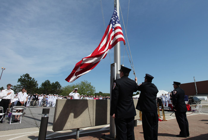 Brunswick Naval Air Station firefighters lower the American flag today at a ceremony marking the official closing of the base.