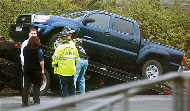 Massachusetts State Police officers stand by as a Toyota pickup truck is placed on a tow truck in a rest area along Interstate 495 in Chelmsford, Mass., today. Authorities had been searching for a blue Toyota Tacoma pickup truck seen near where the body of a young boy was found Saturday in South Berwick, Maine.