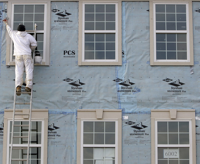 Yuri Kyryk, 25, paints window frames on new condominiums today in Pepper Pike, Ohio. Employers added more than 200,000 jobs in April for the third straight month, the biggest hiring spree in five years.