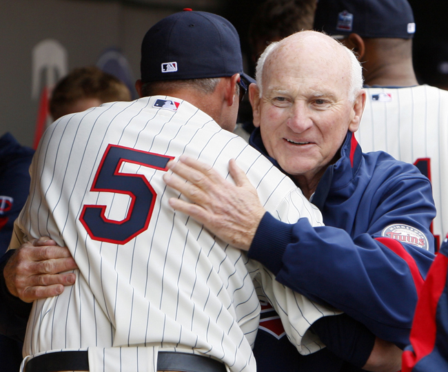 In this April 12, 2010, photo former Minnesota Twins baseball great Harmon Killebrew gets a hug from current Twins player Michael Cuddyer in the dugout prior to a Twins' game against the Boston Red Sox in Minneapolis.