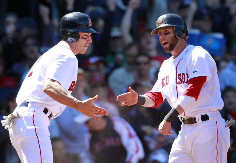 Jacoby Ellsbury, left, and Dustin Pedroia celebrate after scoring on an RBI double by David Ortiz in the third inning today in Boston against the Mariners. Boston won 3-2.