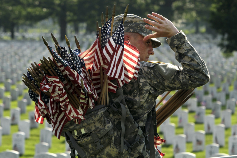 Army Spc. Justin Immerso reaches for a flag to place in front of a head stone at Arlington National Cemetery in Arlington, Va., in preparation for Memorial Day. Every year, on the last Monday in May, Americans pause to pay respect to the men and women who have died while serving their nation in the military.