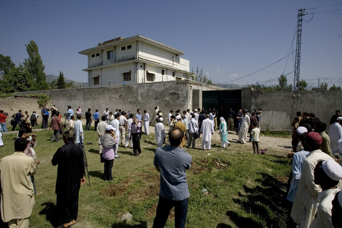 In this photo take Tuesday, local people and media gather outside the perimeter wall and sealed gate of the compound where Osama bin Laden was killed.