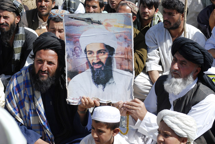 Supporters of Pakistani religious party Jamiat Ulema-e-Islam hold al-Qaida leader Osama bin Laden's picture during a rally in Kuchlak, Pakistan, today.