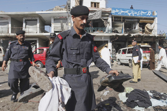A soldier of the Pakistani paramilitary force collects the belongings of his colleagues after the bombing in Shabqadar near Peshawar today.