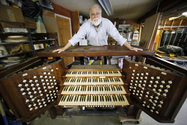 John Bishop, executive director of the Massachusetts-based Organ Clearing House, poses with the console of an 1846 Aeolian Skinner organ in Newcastle, Maine. The organ, which is being refurbished by Bishop, was donated by Trinity Wall Street to Johns Creek United Methodist Church in Georgia.
