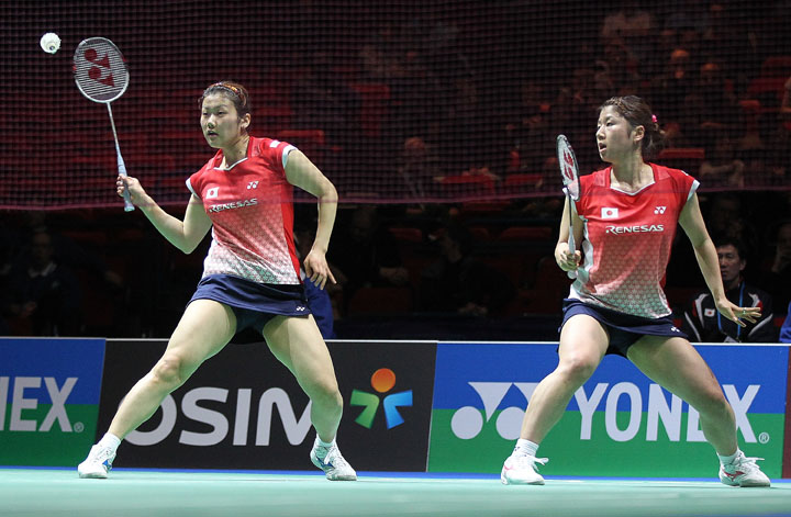 Japan's Reika Kakiiwa, left, hits a shot as her partner Mizuki Fujii looks on during their women's doubles quarterfinal match at the All England Badminton Championships in Birmingham, England.