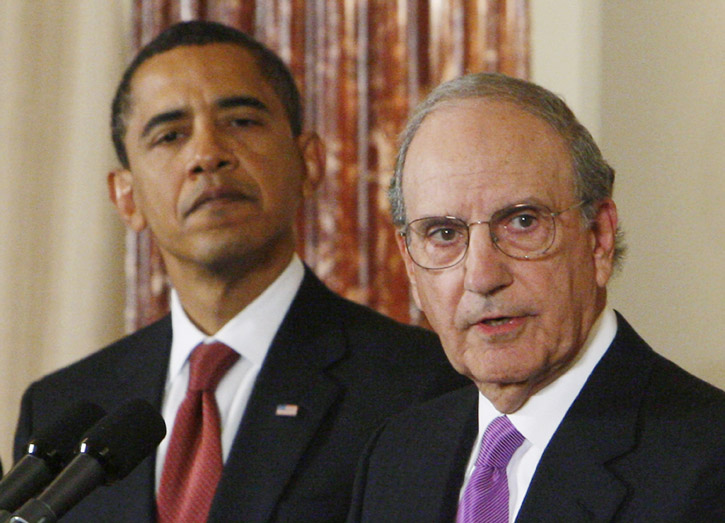 With President Barack Obama looking on, Middle East envoy George Mitchell speaks at the State Department in Washington in this Jan. 22, 2009, photo.