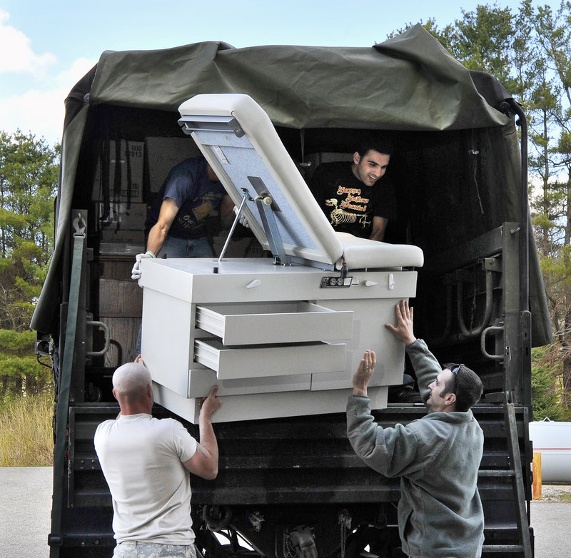 A donated examination table is hoisted into an Army truck by members of the 716 Engineers Battalion and volunteers for Partners for World Health as the group packs donated medical supplies and equipment for shipment to Haiti.