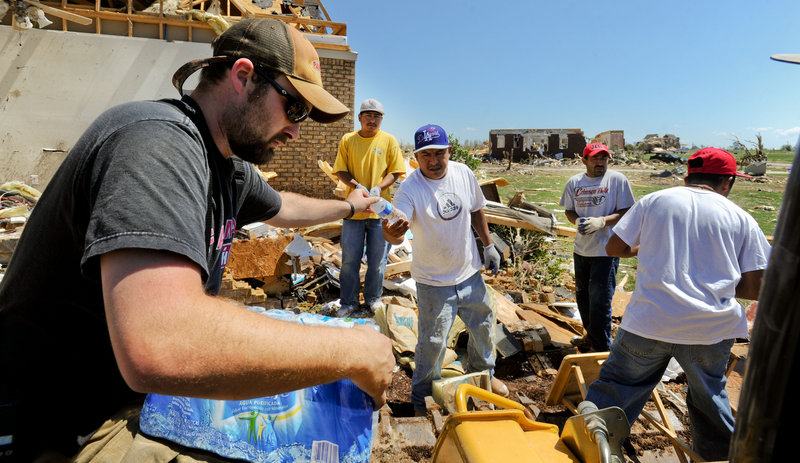 Volunteers fan out through the communities razed by last week's tornado, delivering food and water to victims and volunteers Friday. Daniel Bryant passes out water to Artura Camacho, Miguel Camacho, Hector Martinez and Jesus Amaro, helping at Dwight Henderson's Magnolia Terrace, Ala., home.