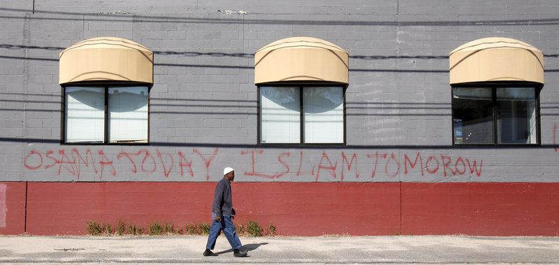 Jirde Mohamed walks past graffiti Monday on the Maine Muslims Community Center on Anderson Street in Portland. The writing reads: