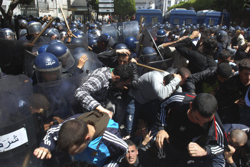 Algerian anti-riot police use batons to disperse students calling for political change during a protest Monday in Algiers.
