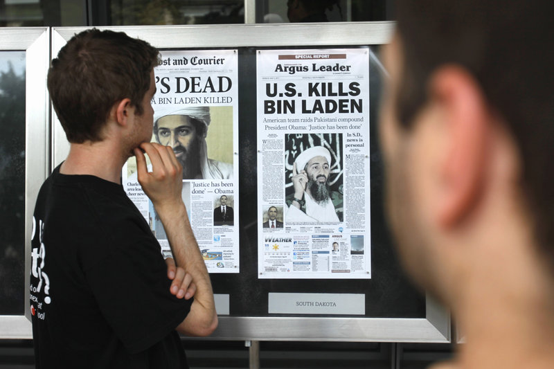 Bryan Byrd, 22, of Washington, left, looks at a display of newspaper front pages at the Newseum in Washington, D.C., on Monday, the day after Osama bin Laden was killed. World reaction ranged from leaders congratulating the United States for its raid in Pakistan to outrage among sympathizers vowing to avenge the al-Qaida leader.