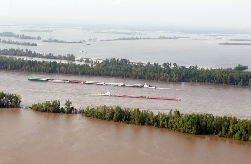 Barge traffic moves along the Mississippi River near Cairo, Ill., last week. Maj. Gen. Michael Walsh, who commands the Mississippi Valley division of the Army Corps of Engineers, decided Monday that the best course to relieve pressure on the flood wall at Cairo was to blow a massive hole in the Birds Point floodway levee in southeast Missouri.