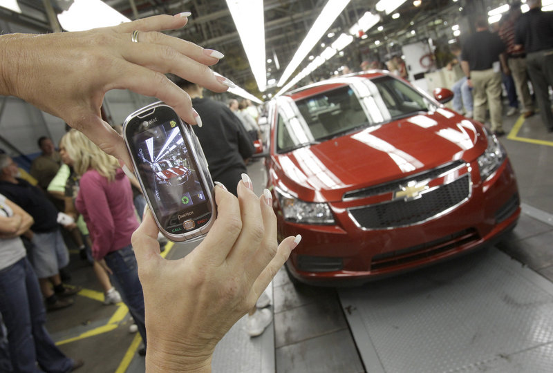 An auto worker photographs the first Chevrolet Cruze compact sedanproduced last September at the GM factory in Lordstown, Ohio. Small vehicles were big sellers in April.