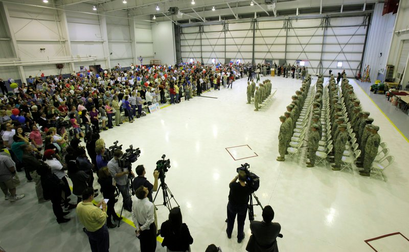 Members of the 94th Military Police Company stand at attention before a welcoming crowd Tuesday inside a hangar at the Manchester Boston Regional Airport in New Hampshire. The unit, which has about 40 soldiers from Maine, spent a year in Iraq providing security and training at bases in Baghdad.
