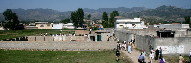 """Local residents and news media gather Tuesday at the compound and house, on right, of Osama bin Laden after authorities allowed people to approach the perimeter of the property in Abbottabad, Pakistan. White House counterterrorism adviser John Brennan said the U.S. already was scouring through items seized in the raid, including computers, DVDs and documents. There was """"more than we were expecting to find,"""" said a U.S. intelligence official who insisted on not being named. """"There's written material, pictures – there's all kinds of stuff."""""""