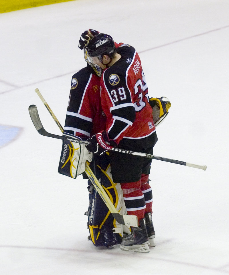 Luke Adam, who scored an early goal, and goalie Jhonas Enroth of Portland embrace Tuesday night after the Pirates brought the series to a sixth game at home with a 6-2 victory against Binghamton.