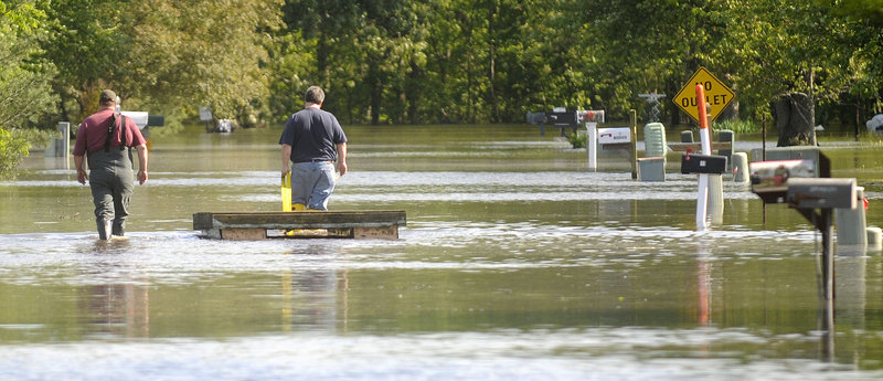 Jeff and Steve Walters float a makeshift platform on Tuesday, trying to save items from a family house in Metropolis, Ill. The Walters had stacked a three-foot sandbag wall around the house, but rising waters overtook it on Monday.