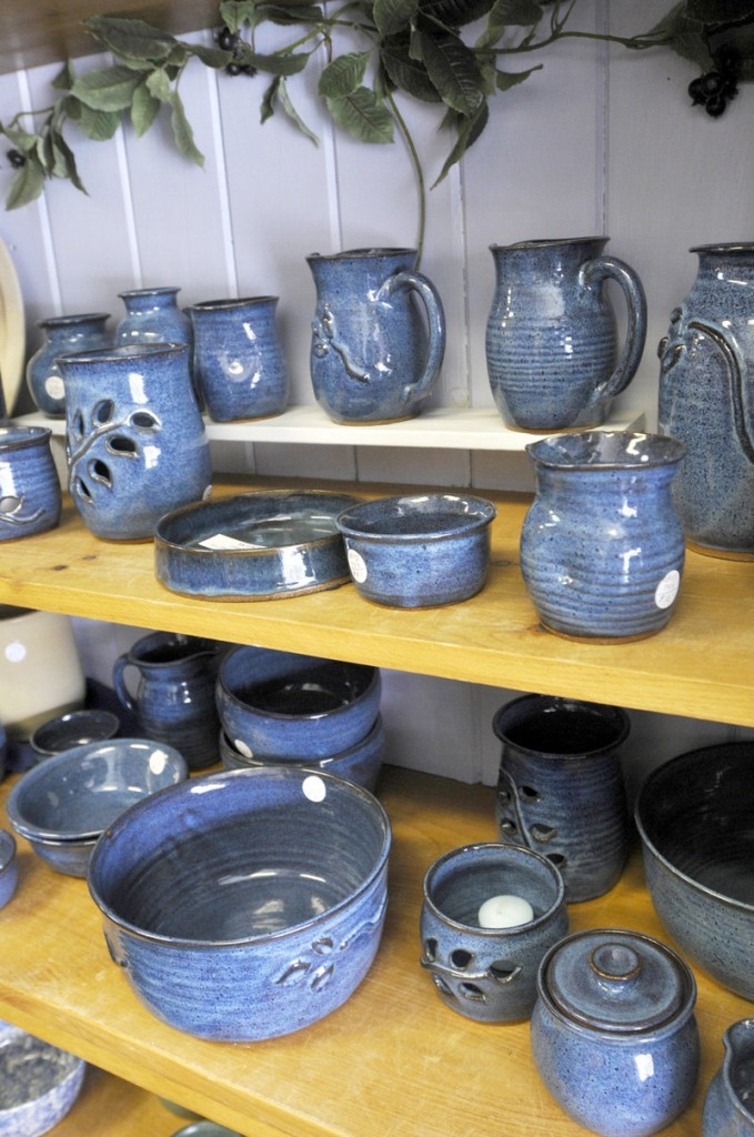 Wheel-thrown stoneware made by Joanne Kenyon is arranged on shelves.