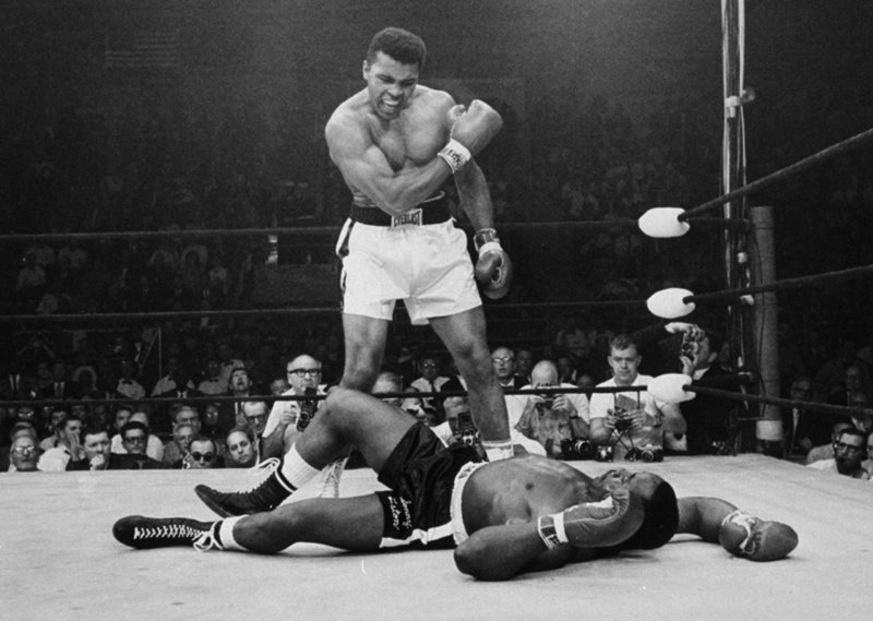 Heavyweight champion Muhammad Ali stands defiantly over fallen challenger Sonny Liston shortly after dropping him with a right hand to the jaw during their historic fight in Lewiston on May 25, 1965. The bout lasted only 1 minute into the first round. Ali is the only man ever to win the world heavyweight championship three times.