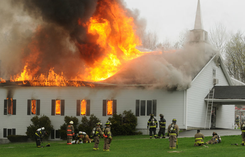 Firefighters from several departments pull back as the roof collapses on the Calvary Apostolic Church in Winterport on Thursday.