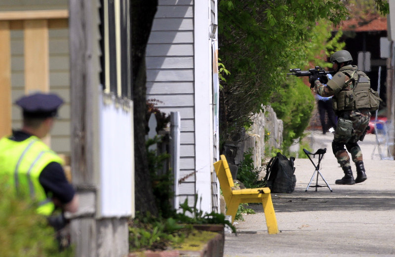 A state police SWAT team member checks a house in Manchester, N.H., on Friday. A standoff with an armed gunman led officials at nearby West High School to cancel classes for the day.