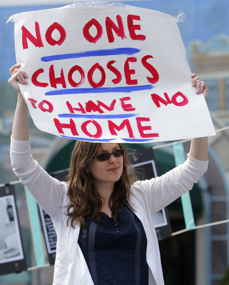 Ashley DeAngelo holds a sign at an affordable housing rally in Portland's Congress Square on Friday.
