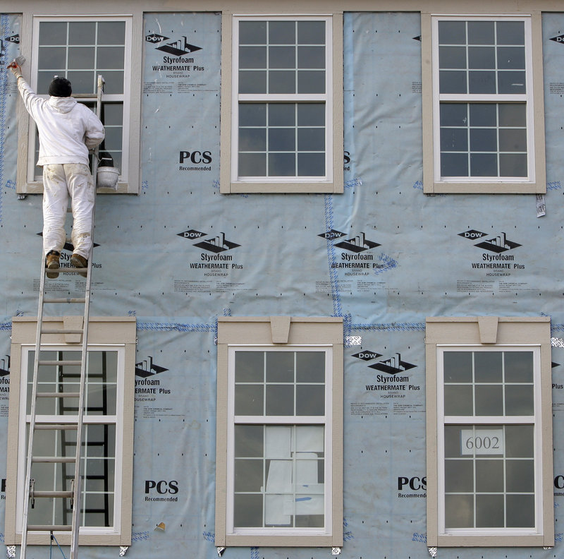 Yuri Kyryk, 25, paints new condominiums Friday in Pepper Pike, Ohio. April was the third straight month in which employers added more than 200,000 jobs.