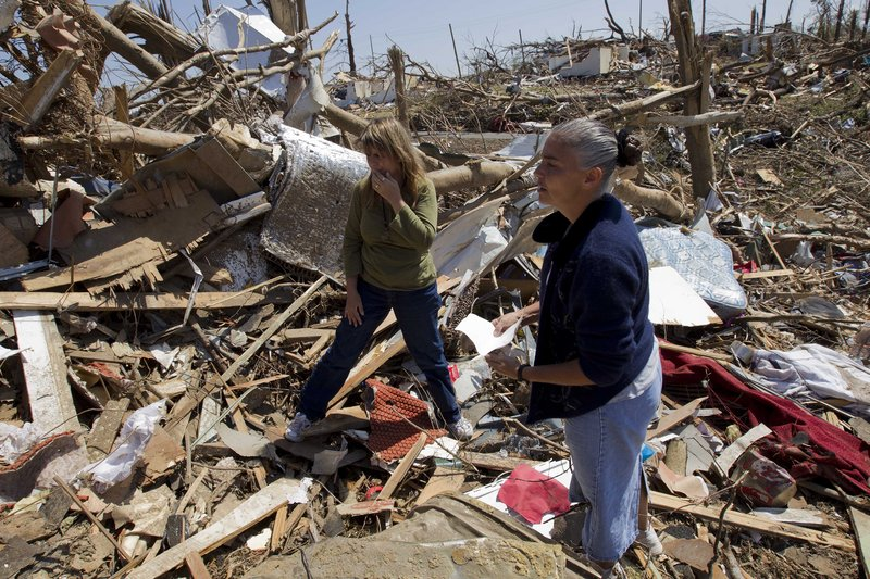 Marie Winnd, right, helps her neighbor Renee Burns search for personal photographs Friday in the wreckage of their homes from storms that struck Pleasant Grove, Ala.