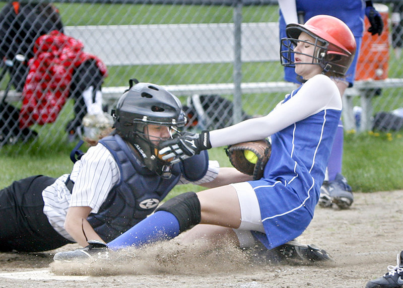 Chelsey Burnell of Sacopee Valley slides under a tag applied by Savanna Poole of North Yarmouth Academy to score Saturday during their Western Maine Conference doubleheader at Yarmouth. Sacopee Valley remained undefeated by winning both games.