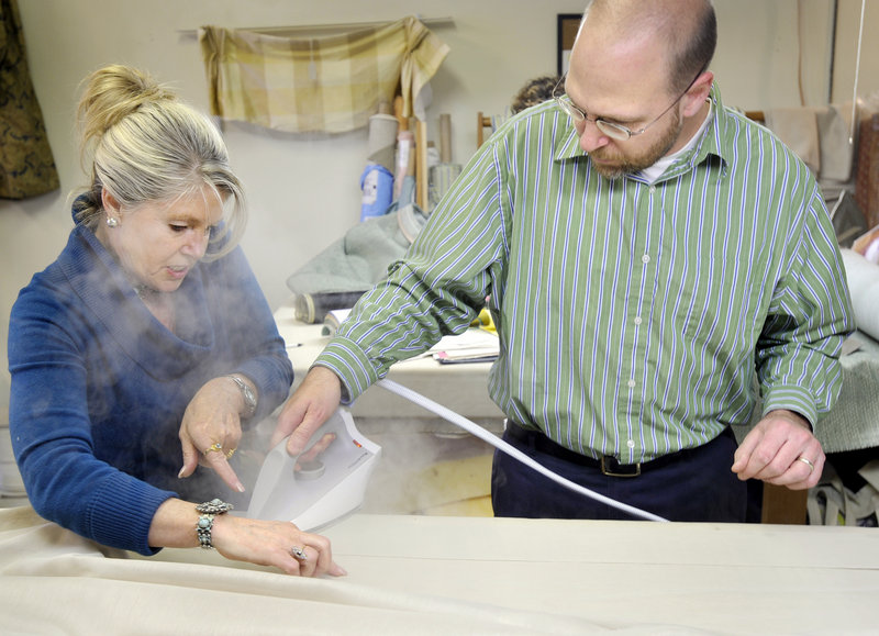 Nancy Seiler, owner of The Drapery Trading Co., gives reporter Ray Routhier some guidance on the finer points of ironing draperies.
