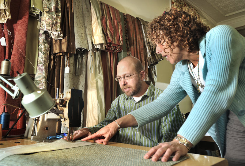 Dana Ben, a seamstress at The Drapery Trading Co., instructs Ray Routhier on how to use a sewing machine.