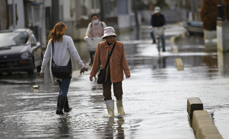 Residents navigate a flooded street last week in Ishinomaki, Miyagi Prefecture, Japan. A part of the city sunk nearly 2 feet 7 inches following the March 11 earthquake and tsunami, meaning neighborhoods are flooded twice a day, during high tide. Scientists say the new conditions are permanent.