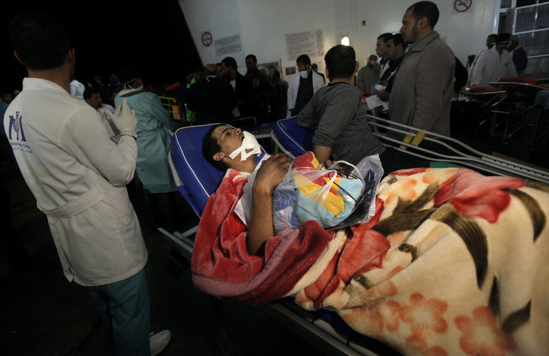 Aid workers in Benghazi, Libya on Monday move an injured man from a boat that evacuated foreign refugees and residents from the besieged port city of Misrata. Moammar Gadhafi's troops have shelled the rebel-held city for weeks.
