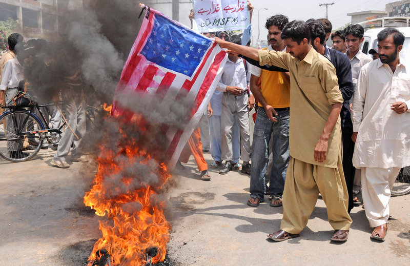 Protesters burn a replica of the U.S. flag at an anti-American demonstration Monday in Multan, Pakistan. Pakistan's prime minister is rejecting allegations that national authorities were either complicit in hiding Osama bin Laden or incompetent in tracking him down.