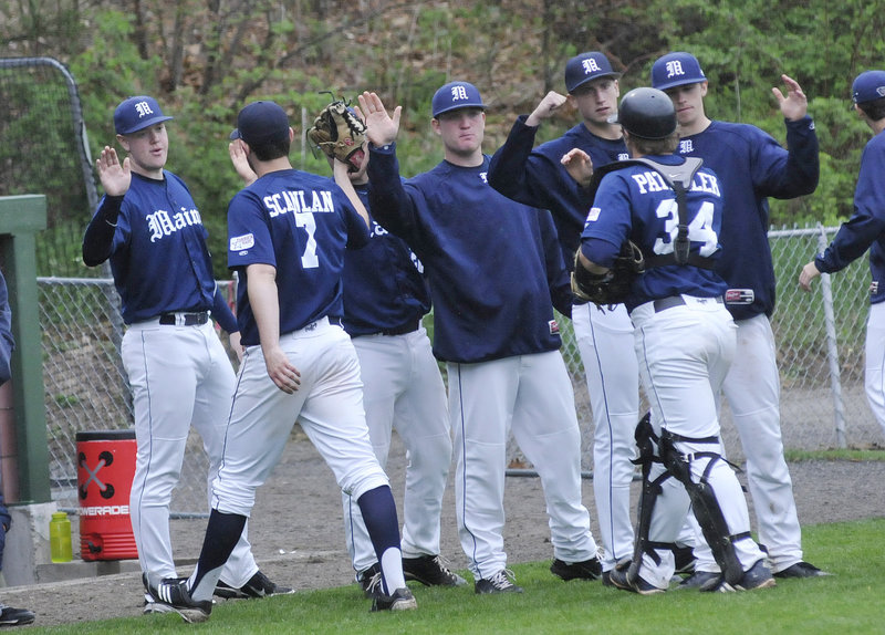 Pitcher Kevin Scanlan, 7, and catcher Tyler Patzalek are greeted by teammates on the way to the Maine dugout at the end of an inning. Scanlan went five innings but was not involved in the decision as Maine rallied in the ninth inning to beat Northeastern, 5-2.