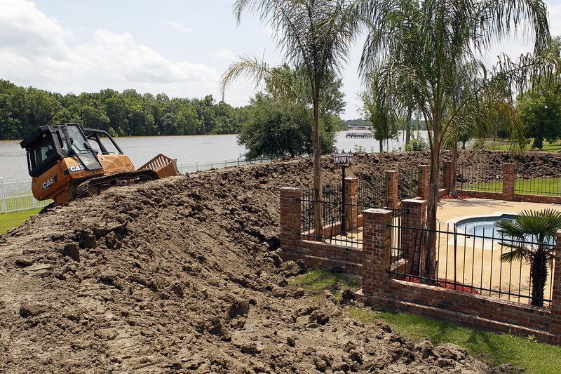 """With the Atchafalaya River in the background, Maxim Doucet builds a levee around his house in Butte LaRose, La., on Wednesday. """"I figured I'd give Mother Nature a run for her money,"""" he said."""