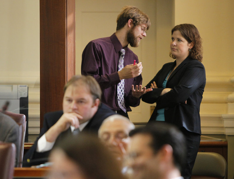 State Rep. Adam Goode, D-Bangor, and House Democratic leader Emily Cain, D-Orono, confer Thursday during a debate on a health care bill at the State House in Augusta. Republicans, who have a narrow majority in the House, rejected six amendments offered up by Democrats in the chamber.