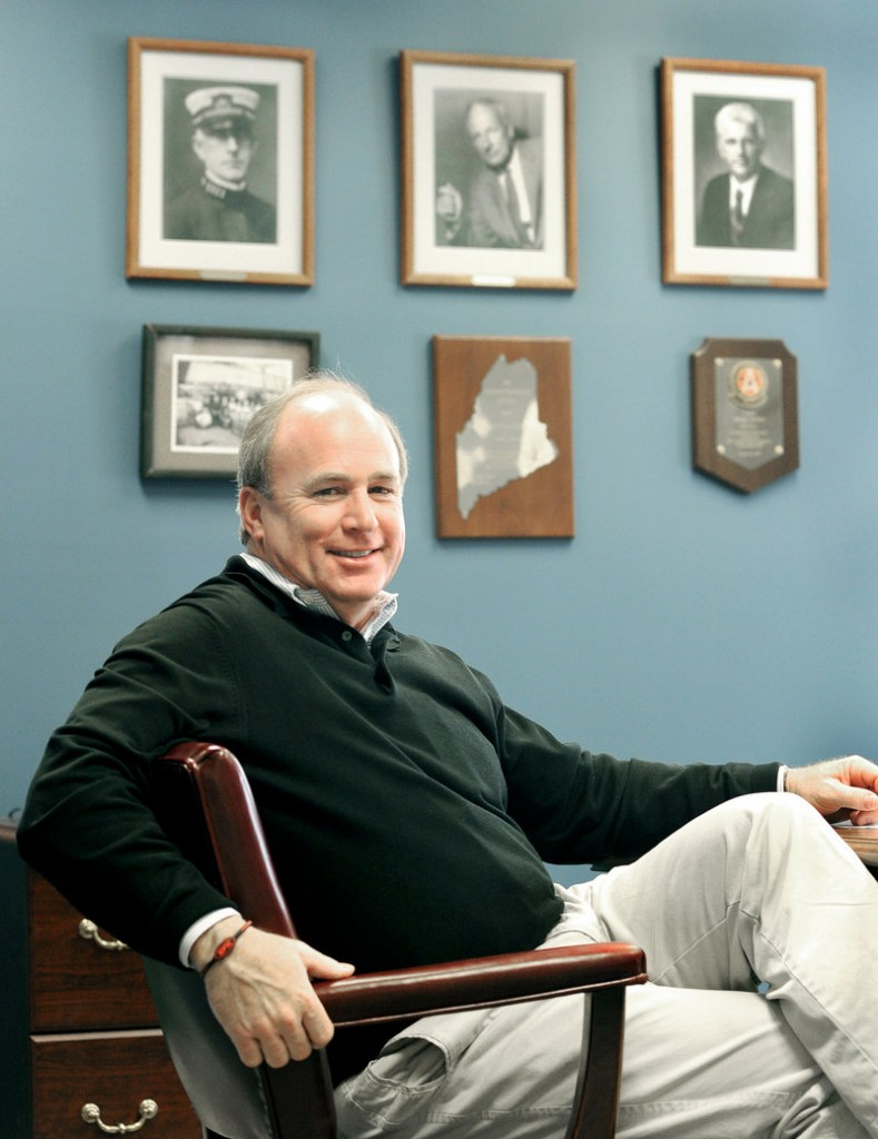 Jackson Parker, president and CEO of Reed & Reed Inc., sits below portraits of the company's founders at its offices in Woolwich.
