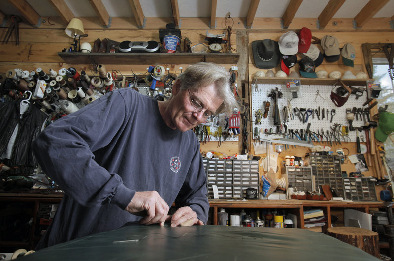 Tim Conn repairs a leather seat cushion at his Buxton shop, North Atlantic Leather & Repair. He also replaces handles on pocketbooks, adds zippers to clothing and mends upholstery.