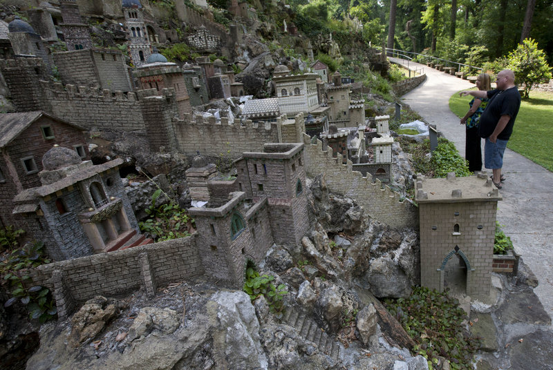 """Diane Moore and John Flannigan tour the Ave Maria Grotto in Cullman, Ala. """"We came out here after the storms to make sure it was still here,"""" Moore said. The concrete miniatures and other treasures were spared by winds that shattered residences and buildings just miles away."""