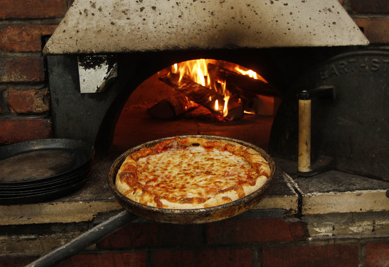A pizza emerges from Dimitri's oven at the Scarborough eatery.
