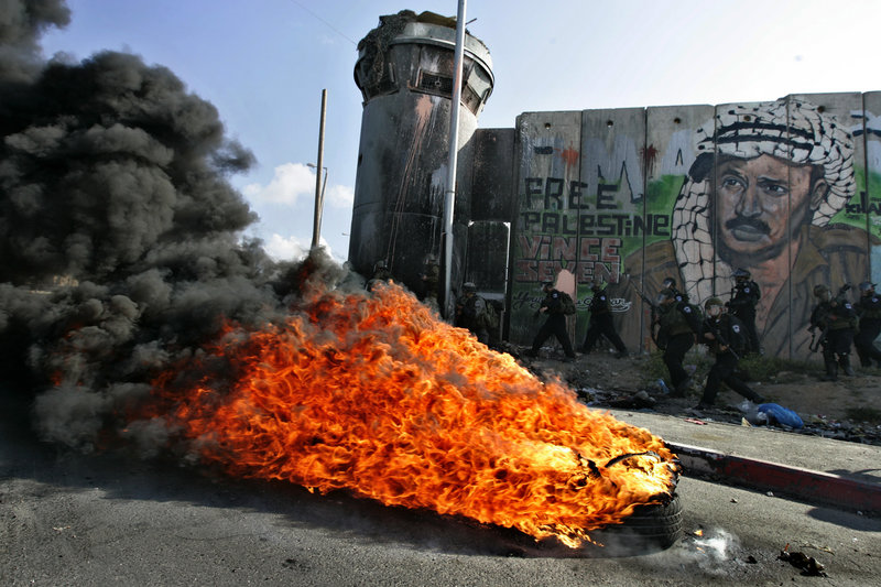 Israeli soldiers run past burning tires under a mural of the late Palestinian leader Yasser Arafat during clashes with Palestinian stone throwers at the Qalandia checkpoint between Ramallah and Jerusalem on Saturday.