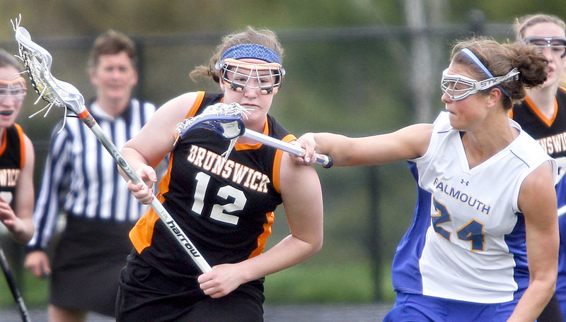 Lydia Caputi of Brunswick runs past Jessica DiPhilippo of Falmouth during the first quarter of their schoolgirl lacrosse game Saturday at Falmouth. Brunswick improved its record to 6-2 with a 10-4 victory. Falmouth is 5-2.