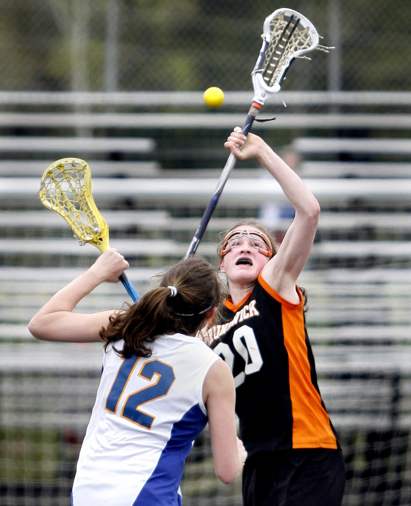 Dakota Foster, right, who scored six of the 10 goals for Brunswick, competes for the ball with Molly Ryan of Falmouth in the first quarter.