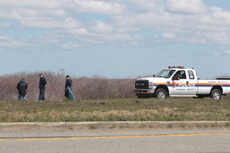 Police officers search for possible victims of a suspected serial killer along Ocean Parkway near Cedar Beach, N.Y., last month.